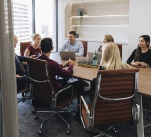 Team communication around boardroom table | Featured image for tips for a successful fitout.