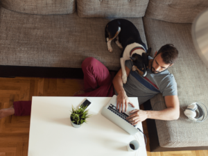 Man uses computer with his dog while working from home.
