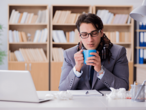 Man in office sips on hot tea | Featured image for healthy office & office wellness.