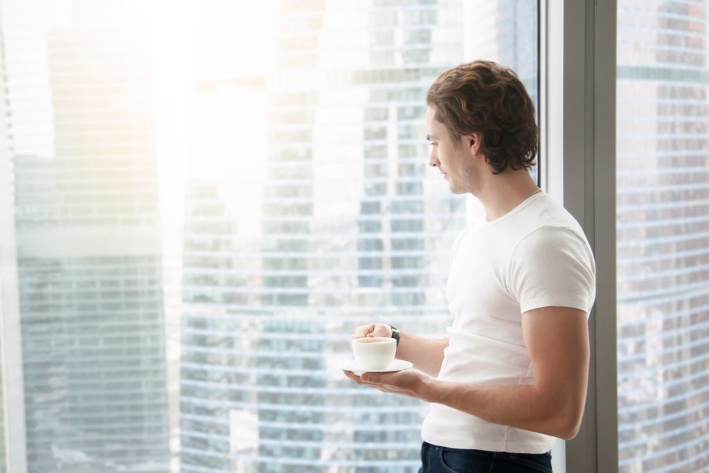 How to get through a crisis - blog featured image showing a young man looking at a sunny day through an office window while sipping a hot beverage out of a cup
